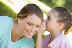 Girl whispering secret into mother's ear at park Stock Photo