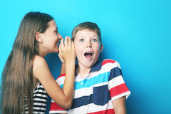 Girl whispering a secret to boy. Young girl whispering a secret to boy on blue background Stock Photography