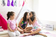 Girl Whispering Secret To Friend By Sister During Pajamas Party. Girl whispering a secret to friend by sister during pajamas party at home stock photography