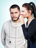 Girl whispering secret to young man. Young girl whispering some secret to young displeased men over blue background Royalty Free Stock Photo