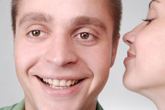 a girl whispering something funny to her boyfrien Royalty Free Stock Photos