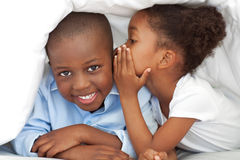 A girl whispering something to her brother Royalty Free Stock Image