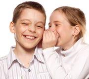 Girl whispers boy in the ear secret Stock Photos