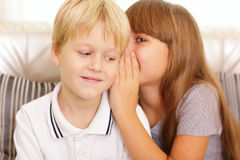 Girl whispers to her brother Stock Images