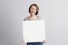 Girl with a white advertising sign. Royalty Free Stock Images