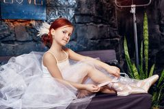 Girl in a white ball gown and shoes, beautiful red hair. Young theater actress. Little prima ballet. Young ballerina girl stock photos