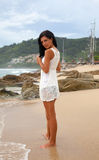 A girl in a white bathing suit walking on the beach stock photo