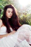 Girl in white. Beautiful young girl in a white dress sitting in the woods and looking down Stock Photography