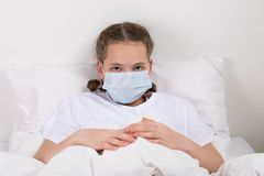 Girl in a white bed covered her face with a mask from germs stock images