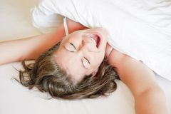 Girl in a white bed yawns and stretches Stock Images