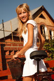 Girl in white with bicycle Stock Photography
