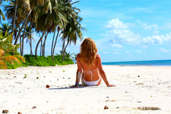 Girl in a white bikini with long hair sits Royalty Free Stock Photo