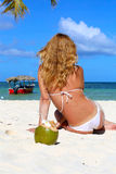Girl in a white bikini sits near the coconut Stock Image