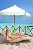 Girl in white bikini sunbathes on a terrace Royalty Free Stock Photo