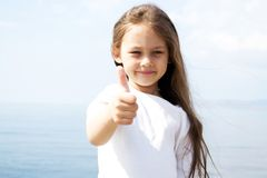 Girl in white blouse. Girl in a white blouse with flowing hair, hand gesture shows that all the great background of the sea Royalty Free Stock Images