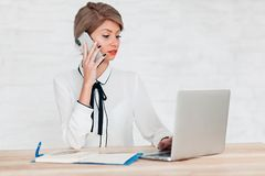 Girl in a white blouse sitting at a table with a laptop talking on the phone royalty free stock photo