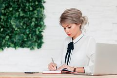 Girl in a white blouse sits at a table with a laptop and writes in a red notebook. A girl in a white blouse is sitting at a table with a laptop and a blue stock photos