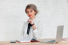 Girl in a white blouse is sitting at the table with a laptop, notepad and phone royalty free stock photo