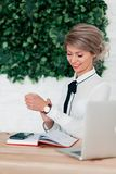 Girl in white blouse sitting at table with laptop, red notepad and phone stock images