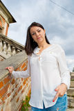 Girl in a white blouse standing on stone stairs Royalty Free Stock Images
