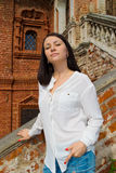 Girl in a white blouse standing on stone stairs Stock Image