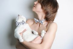 Girl with blue-eyed cat. In the same bow ties polka dot. Without clothing. Fashionable double-look. White background. Girl with white blue-eyed cat on her hands Royalty Free Stock Photo