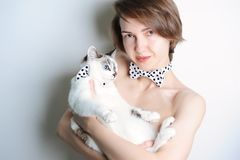 Girl with blue-eyed cat. In the same bow ties polka dot. Without clothing. Fashionable double-look. White background. Girl with white blue-eyed cat on her hands Stock Image