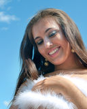 Girl in a white boa. The young beautiful girl in a white boa against summer sky Royalty Free Stock Photography