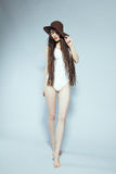Girl in a white body with a hat. Girl with long hair in a white bodysuit and hat Stock Image