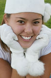 Girl with white cap and gloves. Portrait of a pretty young teenage girl wearing a white knit cap and white gloves Stock Photography