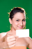 Girl with white card. Beautiful girl holding white card on green background Stock Photos