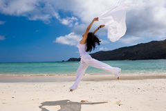 Girl with white cloth jumping on the beach Royalty Free Stock Images