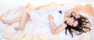 Girl in a white cloth lies on fabrics Royalty Free Stock Photos