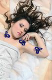 Girl in a white cloth lies on fabrics Stock Photography