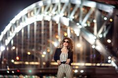 A girl in white clothes with black stripes stands against the background of the bridge