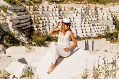 Girl in white clothes posing on white marble quarry, view to the side Royalty Free Stock Photos
