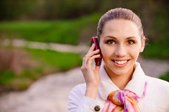 Girl in white coat with phone Royalty Free Stock Images