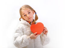 Girl in white coat showing red heart