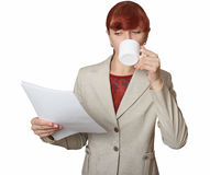 The girl with a white cup in a hand. The business woman with documents drinks from a white cup Royalty Free Stock Photography