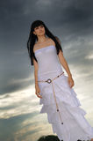 Girl in white dress. Against the dark sky Stock Image