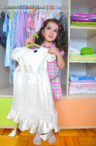 Girl with white dress. Little girl with white dress in her hand Stock Photo
