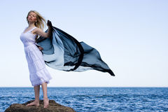 The girl in a white dress. Holds a scarf on a wind Stock Image