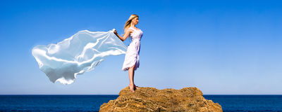 The girl in a white dress. Holds a scarf on a wind Royalty Free Stock Photo