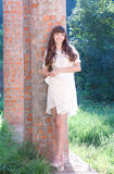 Girl in a white dress against a brick wall Royalty Free Stock Photo