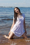 Girl in a white dress ashore Stock Photos