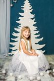 Girl in white dress on the background of the Christmas tree. The girl in white dress on the background of the Christmas tree Stock Photo