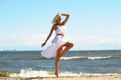 Girl in a white dress on the beach Stock Image