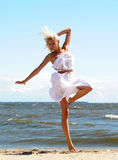 Girl in a white dress on the beach Stock Images