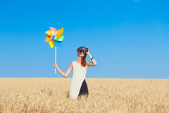 Girl in white dress with binocular and wind toy Stock Photo