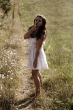 A girl in white dress blowing dandelion royalty free stock images